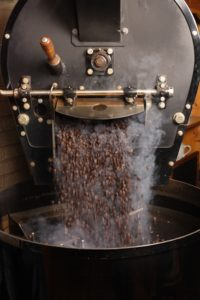 The freshly roasted coffee beans from a large coffee roaster being poured into the cooling cylinder.